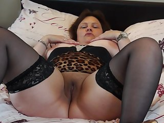 Tattooed mature Tiger Cub licks her tits and strokes her pussy