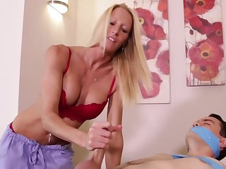 Submissive client receives a handjob by the blonde masseuse